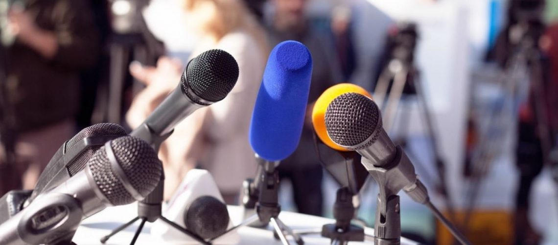 Media-relations-press-conference-microphones-on-table-2-Shutterstock-514070581